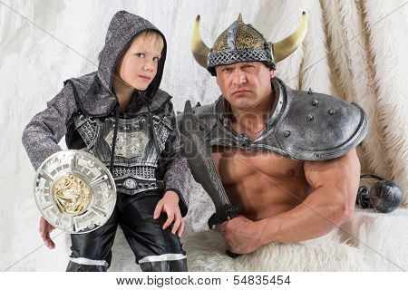 A menacing muscular man with young son in costume viking with a sword