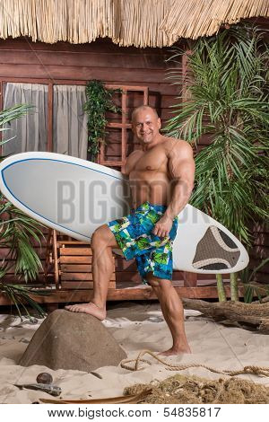 Muscular man on a sandy beach with a surfboard in hand