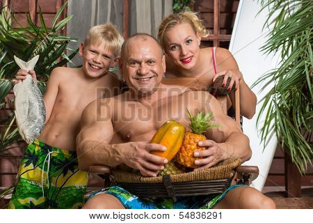 A family of three on a beach with a basket of fruit