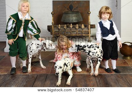Two happy boys and little girl in medieval costumes play with three dalmatians sit near fireplace.