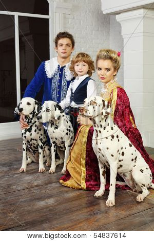 Young father, mother and little son in medieval costumes near window with three dalmatians.