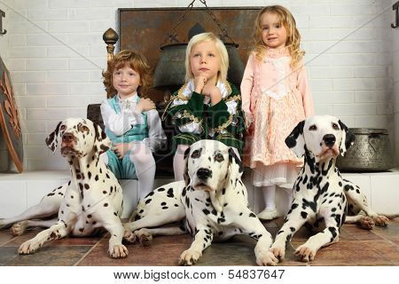 Two boys and little cute girl in medieval costumes and dalmatians sit near fireplace with hanging boiler.