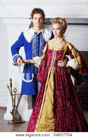 Young couple in colored medieval costumes stand next to fireplace.