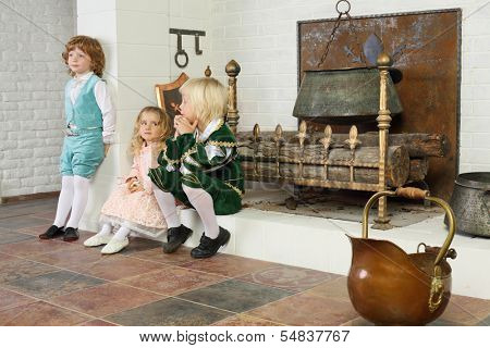 Two boys and girl in medieval costumes sit near fireplace with logs and hanging pot.