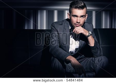 Portrait of a handsome man in a suit who sits in the spotlight over a striped background
