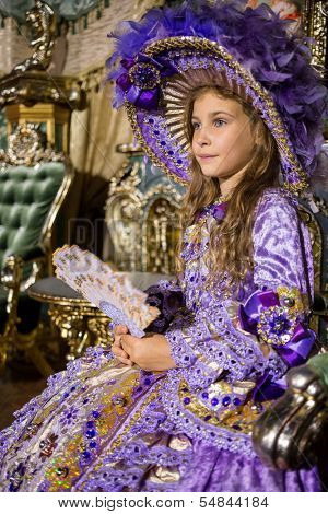 The girl in old-fashioned dress  with fan sitting in beautiful room with gilded furniture