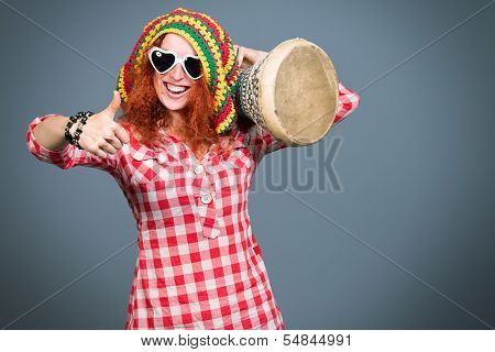 Portrait of a rastafarian girl playing her drum.