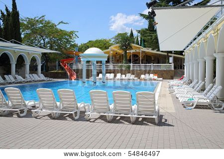 YALTA - AUG 21: Blue swimming pool with loungers around in Marat Hotel on August 21, 2013 in Yalta, Ukraine.
