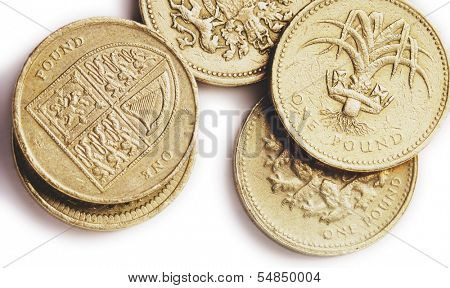 An assortment of British one pound coins, one showing the UK coat of arms, representing the four nations, England, Ireland, Scotland and Wales,another showing a leek, the national plant of Wales.