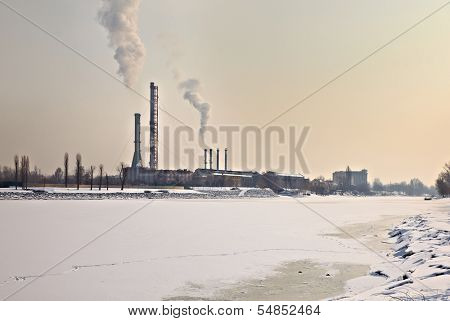 Power station in winter by a frozen river