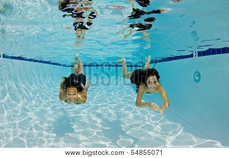Smiling Girls Swimming Underwater