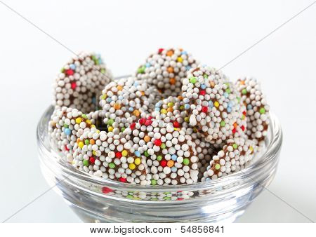 portion of chocolate cookies with colorful smarties, in a glass bowl