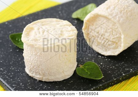 detail of two goat cheeses on a plastic cutting board