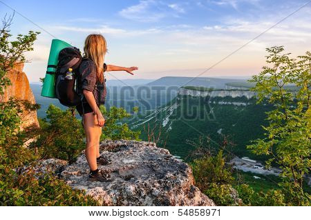 Young hiking woman in the rays of sunset, standing at the top of Tope Kermen, Crimea, Ukraine