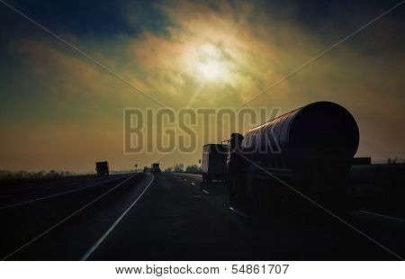 Gasoline tanker rides the highway in the evening sun rays