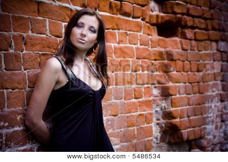 Charming Woman Near Brick Wall