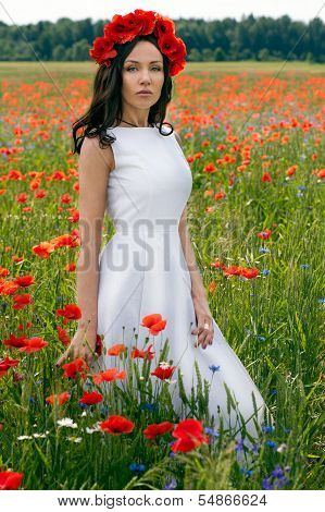Beautiful Young Brunette Girl Wearing White Summer Dress And Flower Chaplet In Poppy Filed