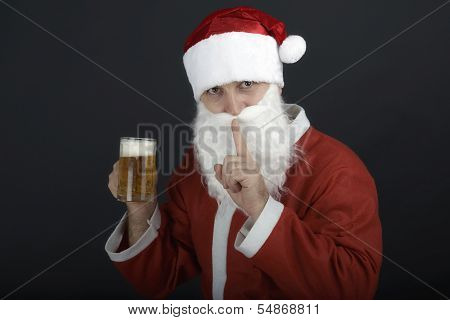 Santa Claus holding  a large glass of beer.