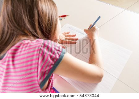 Child Writing Her Homwork At A Desk With A Blue Pencil Crayon