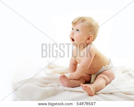 Portrait of cute baby boy look up sitting on plaid, adorable child closeup