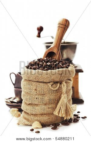 Coffee beans in burlap sack with wooden scoop  over white