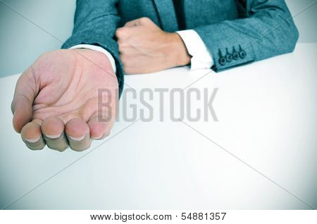 man wearing a suit sitting in a table with an outstretched hand