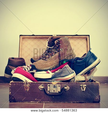 a pile of shoes in an old brown suitcase with a retro effect