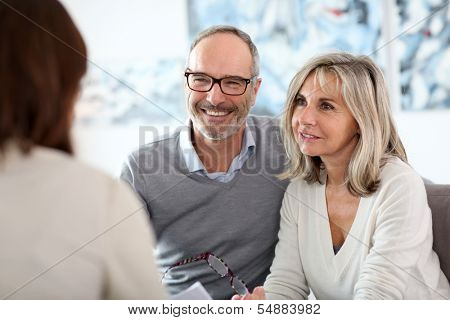 Senior couple meeting financial adviser for investment poster