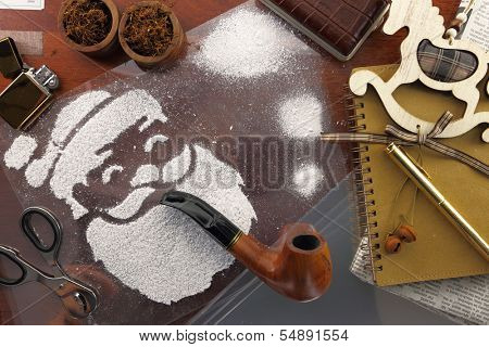 Santa made of snow spray smoking pipe on wooden desk with items