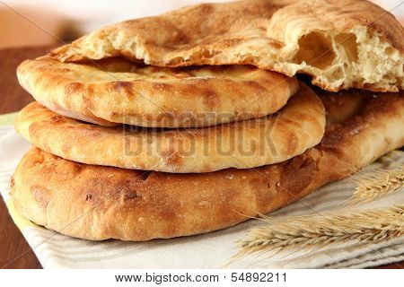 Pita breads with spikes on table on bright background