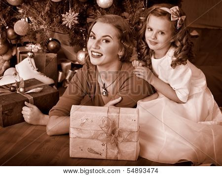 Child with mother receiving near Christmas tree. Black and white retro.