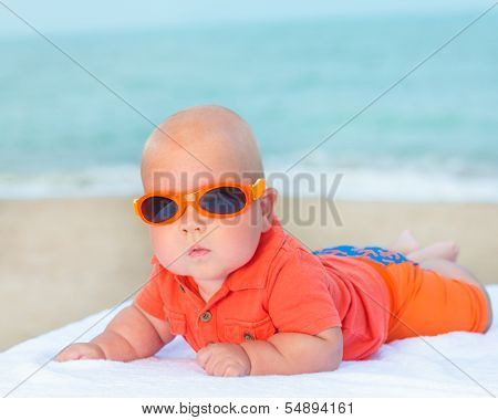 Cute baby wearing sunglasses on the sunbed