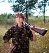 stock photo of shotgun  - Young beautiful girl with a shotgun looks into the distance in an outdoor - JPG