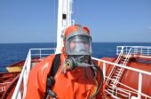 image of decontamination  - man in protectiv suit on deck of chemical tanker - JPG