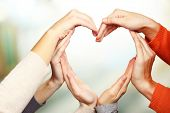 foto of union  - Human hands in heart shape on bright background - JPG