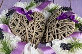 Decorative wreath with wicker hearts on wooden background
