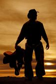 stock photo of western saddle  - a silhouette of a cowboy holding on to his saddle - JPG