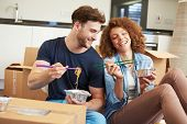 stock photo of takeaway  - Couple Moving Into New Home Enjoying Takeaway Meal - JPG