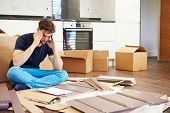 foto of frustrated  - Frustrated Man Putting Together Self Assembly Furniture - JPG
