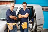 stock photo of teenagers  - Workers In Family Business Standing Next To Van - JPG