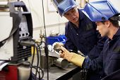 stock photo of manufacturing  - Engineer Teaching Apprentice To Use TIG Welding Machine - JPG