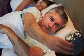 foto of early 50s  - Couple In Bed With Man Reaching To Switch Off Alarm Clock - JPG