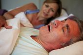 stock photo of annoyance  - Man Keeping Woman Awake In Bed With Snoring - JPG