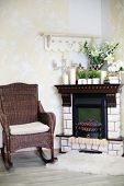 picture of cozy hearth  - Wicker rocking chair and fireplace with candles and flowers in cosy room - JPG