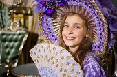 The smiling  girl in old-fashioned dress with fan in beautiful room with gilded furniture