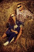 stock photo of haystacks  - Romantic young couple in casual clothes sitting together in haystack - JPG