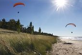 stock photo of glider  - Two Motorized Hang Glider Kites Being Piloted Over Secluded Lake Huron Beach  - JPG