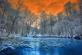 stock photo of snow clouds  - Spectacular orange sunset over white winter forest - JPG