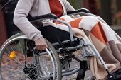 stock photo of disability  - Elder disabled woman in sweter moving on wheelchair - JPG