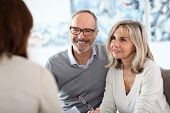 stock photo of smiling  - Senior couple meeting financial adviser for investment - JPG